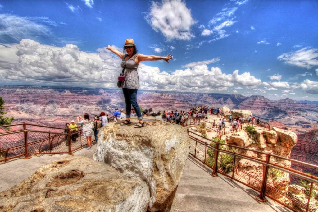 A Tourist on the Grand Canyon South Rim Bus tour enjoys the view at Mather Point