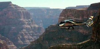 A helicopter flys into the chasm of the Grand Canyon West Rim.