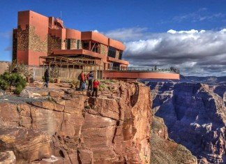 Tourists stand at the edge of the Grand Canyon overlooking the Skywalk.