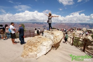 A tourist poses for a fun photo at Grand Canyon Mather Point