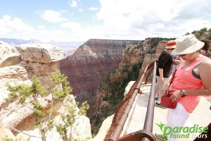 A tourist reaches for her camera to capture the amazing view of Mather Point tucked away at the Grand Canyon National Park