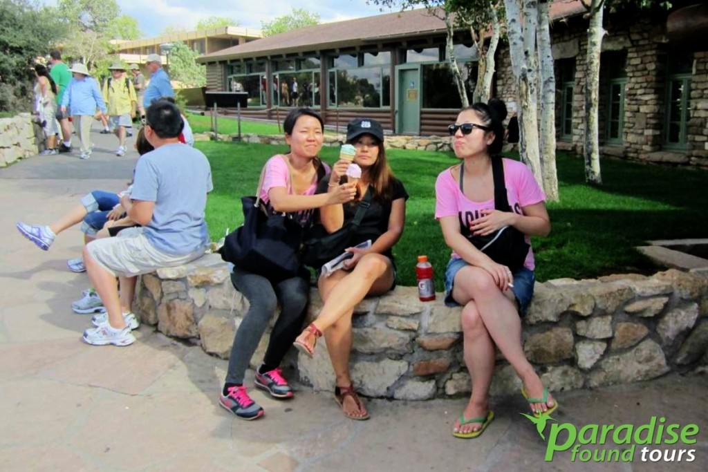 Visitors enjoy ice cream together on warm day behind Bright Angel Lodge